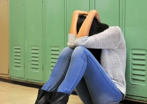 Sad high school girl sitting against locker