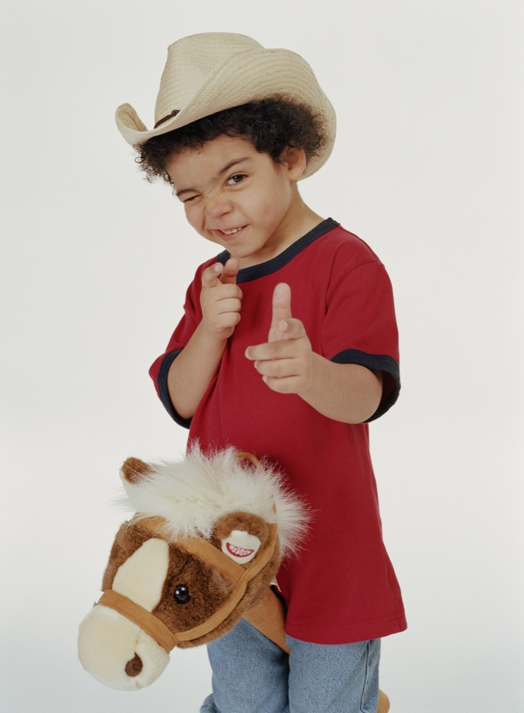 Boy (4-6) riding hobby horse, pretending to shoot, portrait